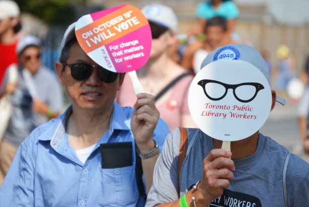 Two people walking in a Labour Day parade. One of them has a small circular sign covering her face with a picture of a pair of glasses on it, and the words library worker on it.