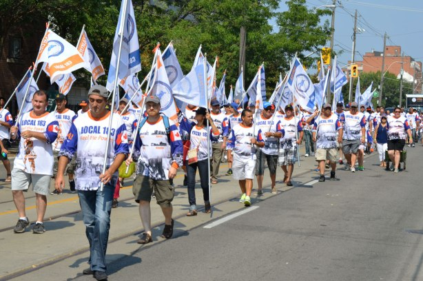 workers from local 183 union walk in a labour day parade while carrying union flags