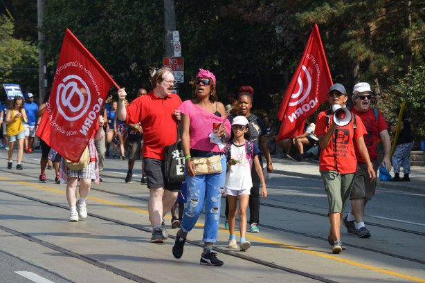 A group of people walk in a labour day parade