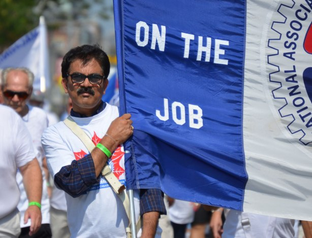 A man holds a banner in the Labour day parade, only part of the banner can be seen but it is for the International Association of Machinists and Aerospace Workers