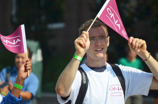 A young man waves a pennant for the ONA, Ontario Nursing Association, as he walks in labour day parade