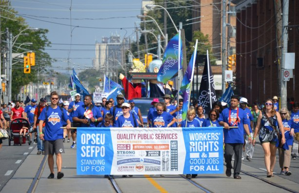 A large group from OPSEU SEFPO union walk in a labour day parade behind a large banner stating Standing Up For Workers Rights and good jobs for all. they are wearing blue t-shirts.