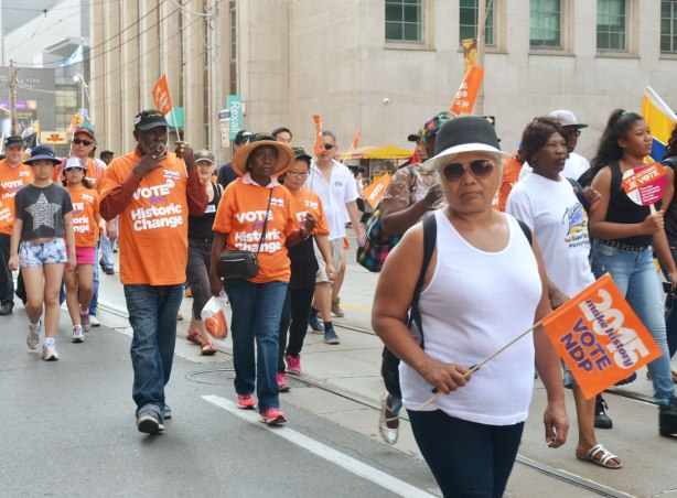 A group of people walks in a labour day parade wearing orange t-shirts and carrying small flags that say Vote for Historic Change