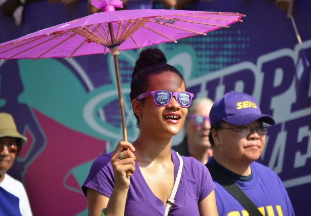 A woman carries a purple parasol as she walks in a labor day parade. She is wearing purple sunglasses that say Agent of Change on them