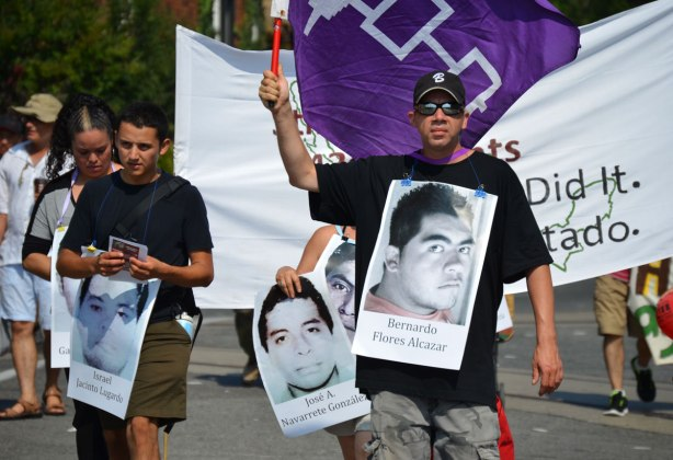 A man carried a purple flag and wears a placard on his front with a picture of man on it. Missing person, Bernardo Flores Alcazar.  The person behind him is holding a picture of Jose A. Navarrete Gonzalez