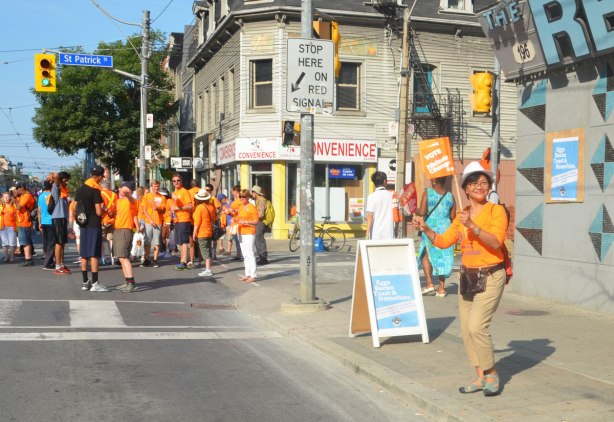 An Asian woman holds two small NDP flags as she stands on a sidewalk on Queen St. West by the Rex bar as she watches a labour day parade