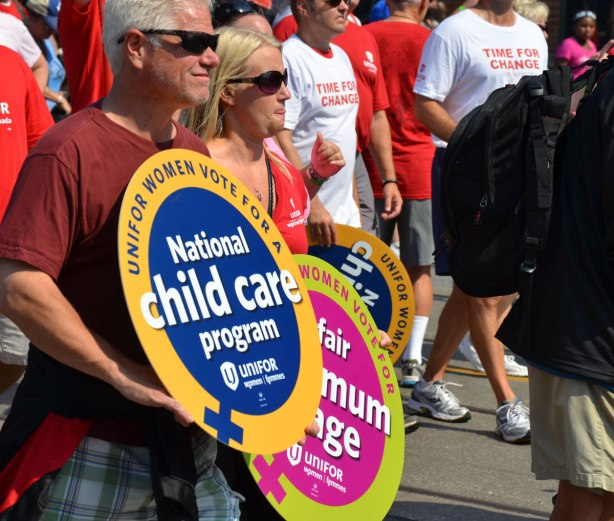Two people in a labour day parade are carrying round signs, one says national health care program and the other says a fair minimum wage.