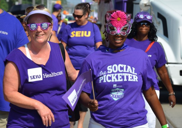 Four women in purple t-shirts from SEIU healthcare union walk in a labour day parade. One woman is wearing sunglasses with agents of change written on them. Another woman has the words The Social Picketer written on the front.