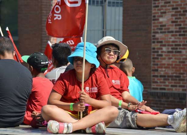 A girl in a blue hat and holding a unifor union flag sits on a flatbed truck in a labour day parade. An Asian woman sits beside her.
