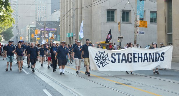 An IATSE union group walks in a parade, Stagehands according to the banner that they are carrying.