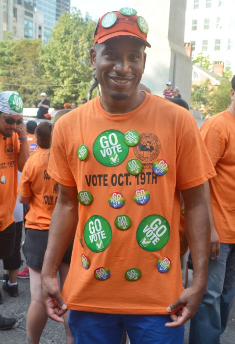 A man is wearing an orange T-shirt with round green stickers and buttons on it. They all say Go Vote