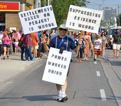 A man who is walking in a labour day parade is carrying three signs, first Pwer work union, second Settlements based on perjury is wrong and third supressing evidence is wrong