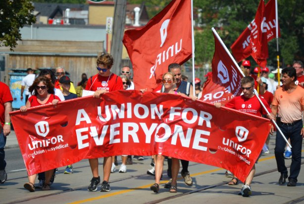 A group walks in a labour day parade, they are carrying a red banner that says A union for everyone. THey are also carrying red unifor flags.