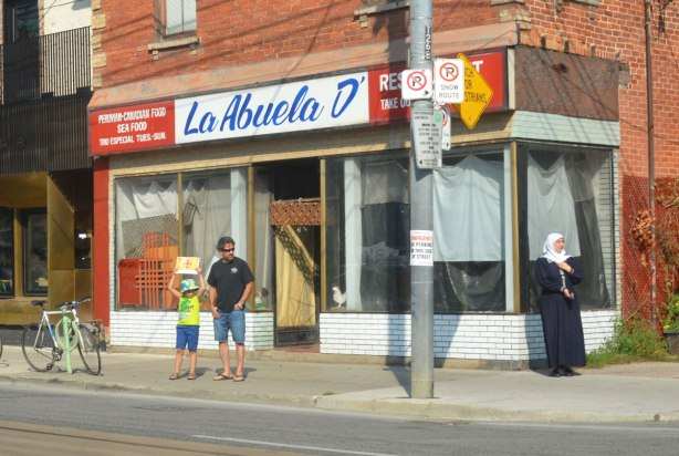 Three people stand on the sidewalk by La Abuela, a Peruvian restaurant. A young girl is holding a CBC sign above her head while her father stands beside her. A woman in black burka and white head scarf is also on the sidewalk.