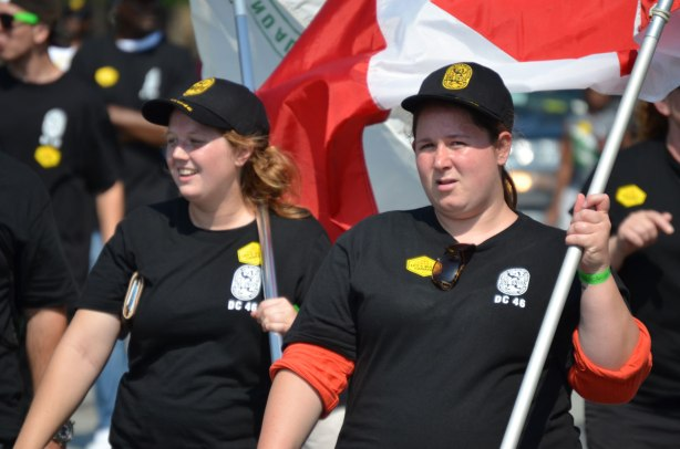 Two women in black caps and T-shirts are walking in a labour day parade. One of them is carrying a Canadian flag