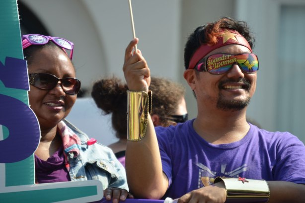 Two people in a labour day parade. The man is wearing wonder woman sunglasses.