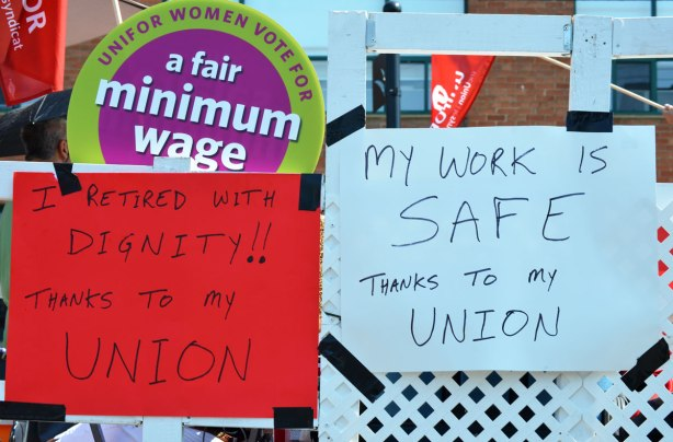 Labour Day parade - hand written signs on the side of a truck that say, My work place is safe thanks to my union, and, I retired with dignity thanks to my union