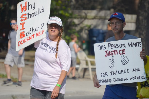 Labour day parade - two marchers, one with a sign that protests agains the WSIB and the other person's sign says This person wants justice for injured workers