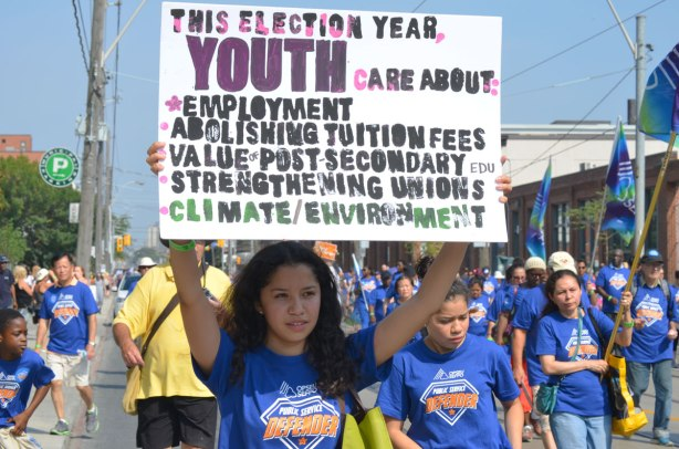 A young woman is holding up a sign about youth cares about and then it lists a few things like employment, tuition fees, unions, climate and the environment, at a Labour day parade