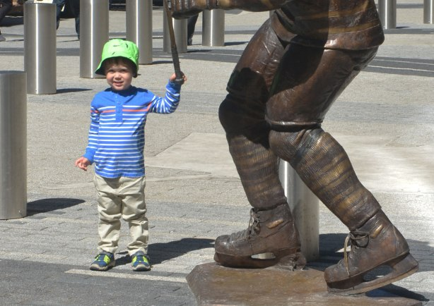 A little boy stands beside a statue of a hockey player where only the legs and skates of the player are in the picture. The boy is holding onto the end of the player's hockey stick