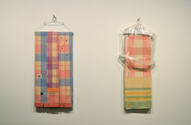 art installation at the Art Gallery of Ontario by Liz Magor - two hangers with plaid blankets folded over them hanging from hooks on a wall. One of the blankets has a clear plastic Creeds bag over the top part of it