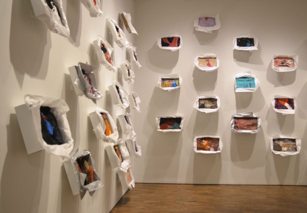 art installation at the Art Gallery of Ontario by Liz Magor - two walls with many open boxes on them. The boxes are made to look like they've just been opened to reveal a sweater or top folded neatly inside, including the tissue paper that often accompanies a new purchase. The clothes have all been decorated with different objects.