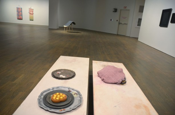art installation at the Art Gallery of Ontario by Liz Magor - in the foreground are two long narrow tables. On one of them is a platter with chocolates and a platter with the remains of cheese and crackers.