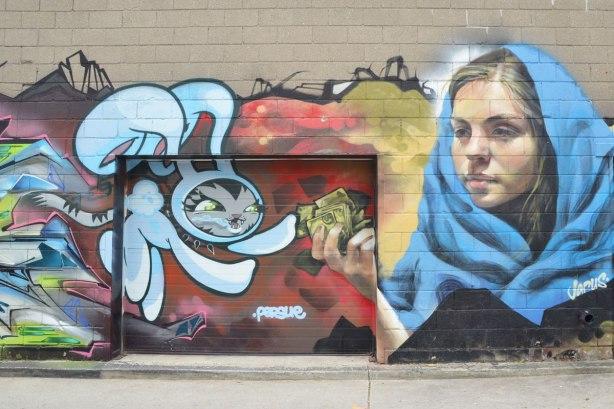Street art on a wall in an alley, A Jarus woman with a blue shawl around her shoulders and a persue rabbit reaching for money that the woman is holding in her hand.