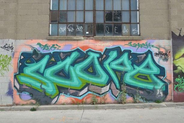 tag-like street art under a window in an alley
