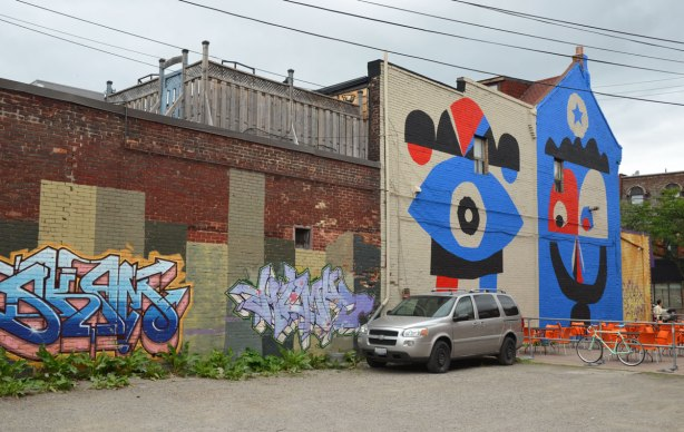 vacant lot, with a grey van parked in it, two pieces of street art on a wall as well as a large two storey mural