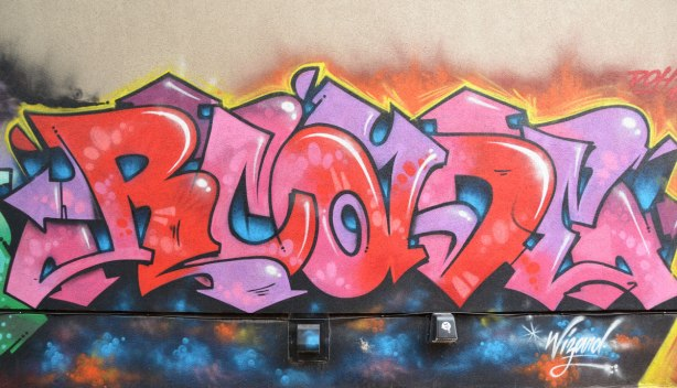 Street art in pinks and reds, signed by Wizard