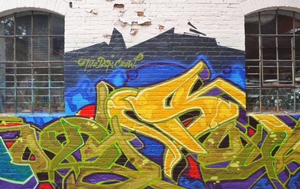 graffiti in yellows and greens on a blue background, on a wall in an alley, between two windows with metal grilles, signed BSM Crew