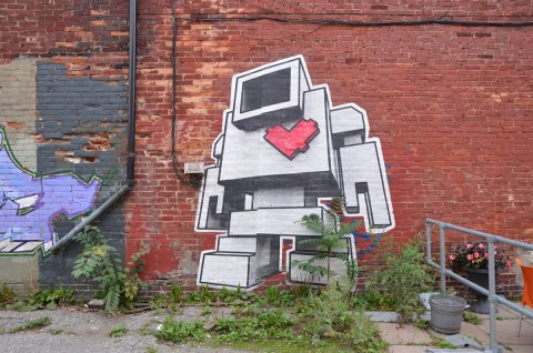 large wheatpaste lovebot on a brick wall