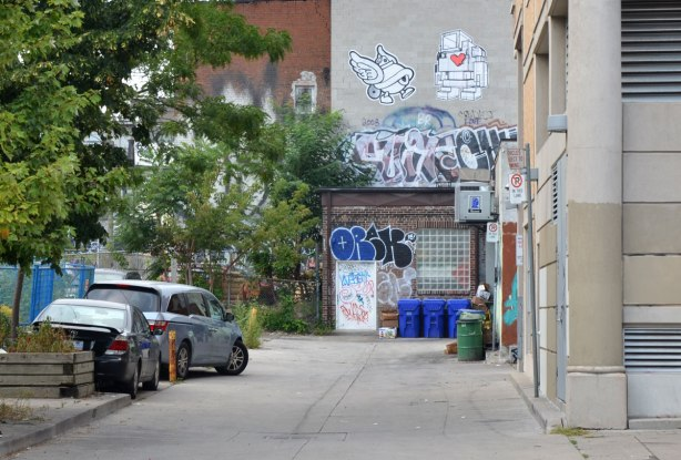 looking towards the end of an alley that has a large wheatpaste 3D lovebot high up on it. Beside lovebot is another wheatpaste