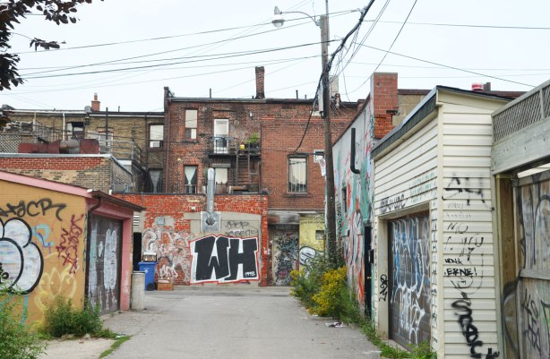 Buildings in an alley with lots of graffiti on them.