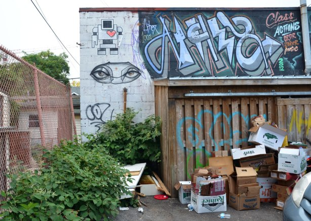 A lovebot and a pair of anser eyes on a wall in an alley. Lots of empty cardboard boxes on the ground by the wall.