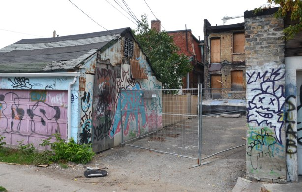 In an alley, the back of a house is being renovated, all the windows are boarded up and some of the exterior brick has been removed. There is a metal gate across the back of the property. The garage to the left is covered with graffiti.