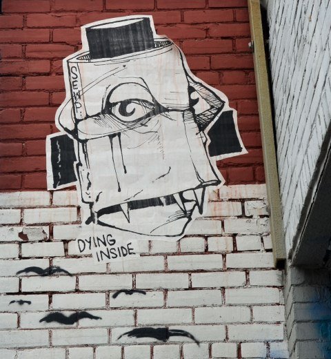 Wheatpaste high up on a wall, a large face like thing. The words 'dying inside' are part of the picture