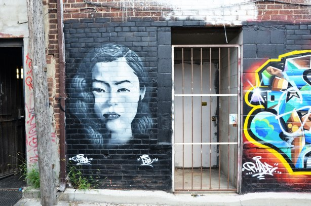 a wall with a painting of a woman's head on the left (in grey tones), a door with metal bar gate in the middle, and part of a tag like graffiti piece on the right.