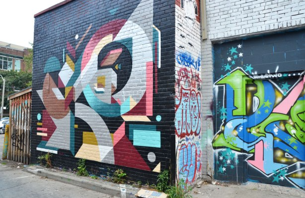 large geometric street art piece on a brick wall in an alley