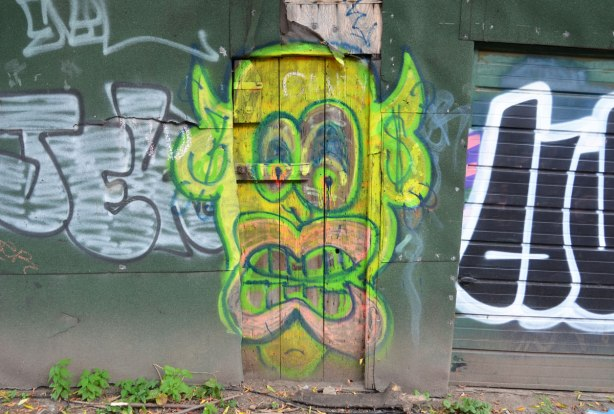 An old wood door on an alley building has been painted with a large yellowish green face with big pink lips and brown teeth