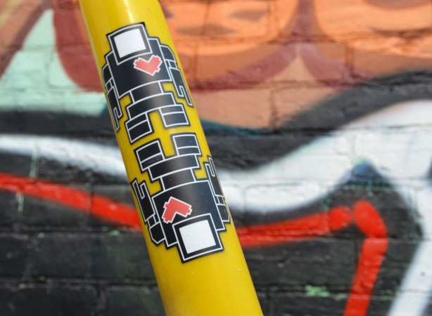 Two black lovebot robot stickers on a yellow protective sleeve around a cable that is helping to hold up a pole.