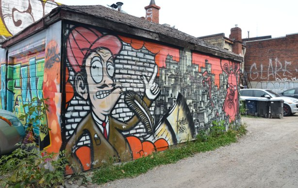 The front and side of a garage are covered with street art. The front is not very very visible in this picture but the side is. A man from the waist up with his finger pointing upwards is beside a picture of city buidings and a poser bunny.
