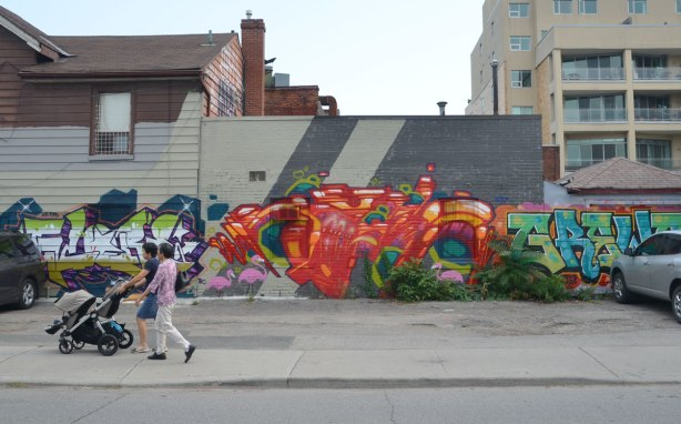 Two women pushing a stroller walk past some street art on Nassau St. in Toronto, a large orange piece ta