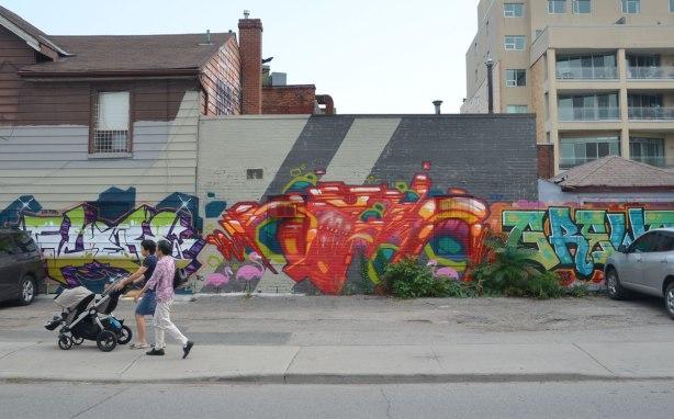Two women pushing a stroller walk past some street art on Nassau St. in Toronto, a large orange piece ta