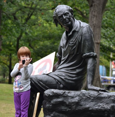 A statue of the Canadian poet Al Purdy sitting in a park. A girl looking at a smartphone is standing by its feet.