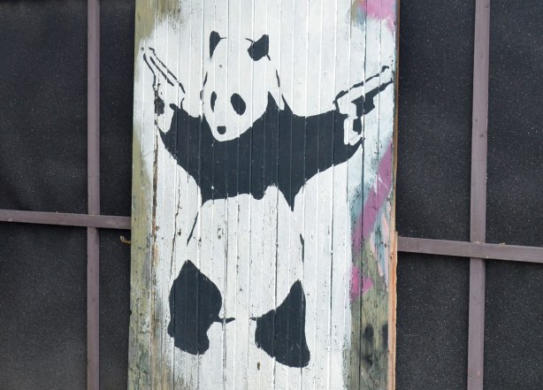 A painting of a panda standing upright, painted on an old wood fence. The panda has a gun in each hand and they are pointed upwards