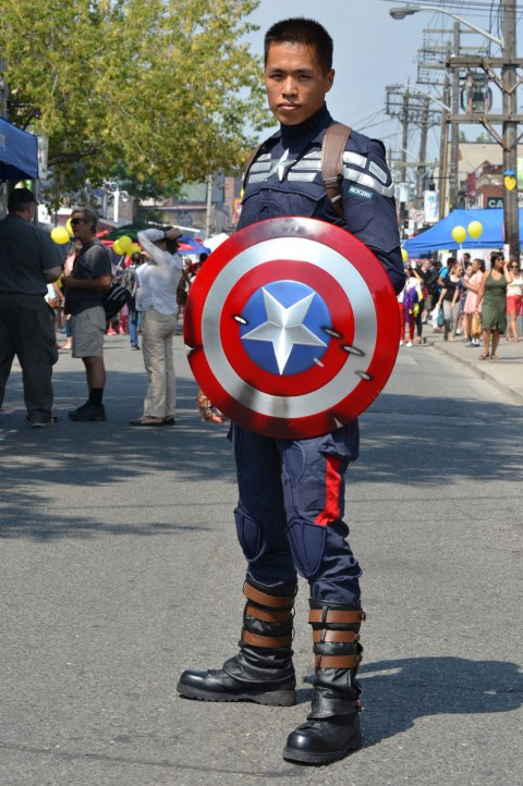 A young man with a Captain America shield, poses in the street