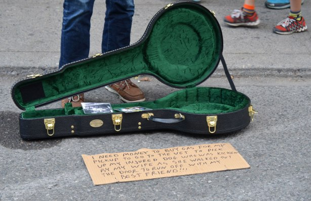 "a street musician stands beside his empty banjo case. In front of the case is a note that says "" I need money to buy gas for my pickup to go to the vet to pick up my injured dog who was kicked by my wife as whe walked out the door to run off with my best friend"""