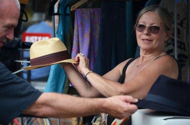 A woman selling hats is holding a straw hat with a black band. A male customer is reaching for a dark blue hat.